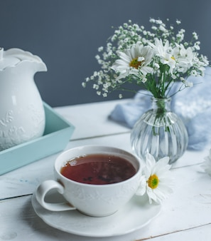 Uma xícara de chá e margaridas brancas em uma mesa branca.