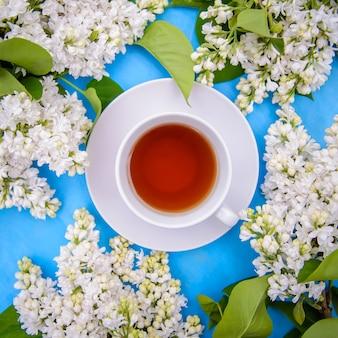 Uma xícara de chá e ramos de persa terry branco lilás em uma vista superior de fundo azul