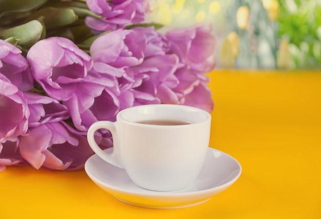 Uma xícara de chá e tulipas violetas na mesa