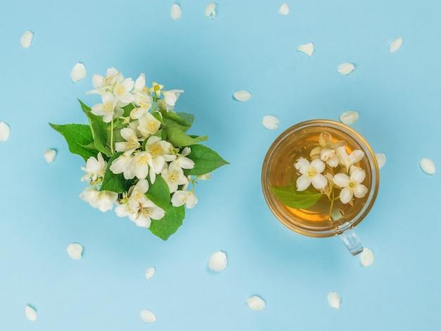 Uma xícara de chá e um buquê de jasmim em uma superfície azul. uma bebida revigorante que faz bem à saúde.