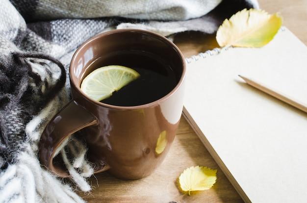 Uma xícara de chá e um caderno vazio para o esboço.