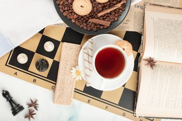 Uma xícara de chá e um livro em um tabuleiro de xadrez
