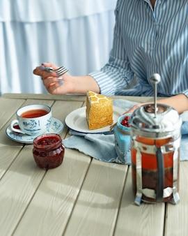Uma xícara de chá e um pedaço de bolo no café
