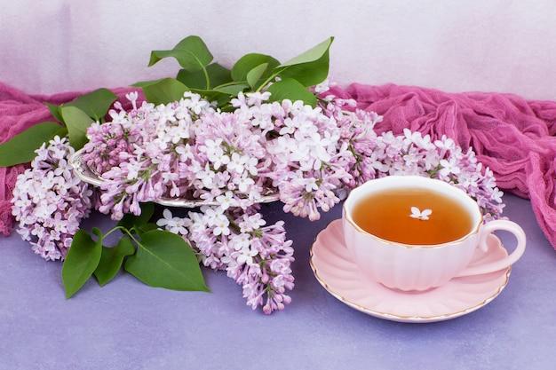 Uma xícara de chá em um copo-de-rosa e um buquê de rosas lilás em um vaso