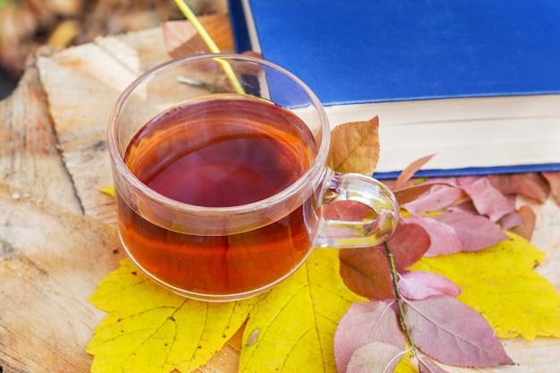 Uma xícara de chá em uma folha de bordo amarela perto de um livro em um toco na floresta de outono_