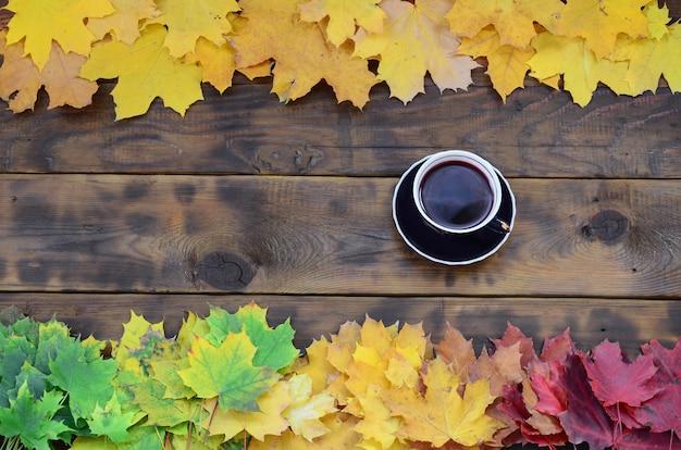Uma xícara de chá entre um conjunto de folhas de outono caído amarelecimento em uma superfície de fundo de tábuas de madeira naturais de cor marrom escuro