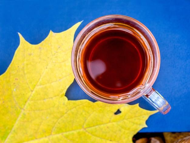 Uma xícara de chá está em um livro na floresta perto de uma folha de bordo amarela. descanse na floresta de outono_