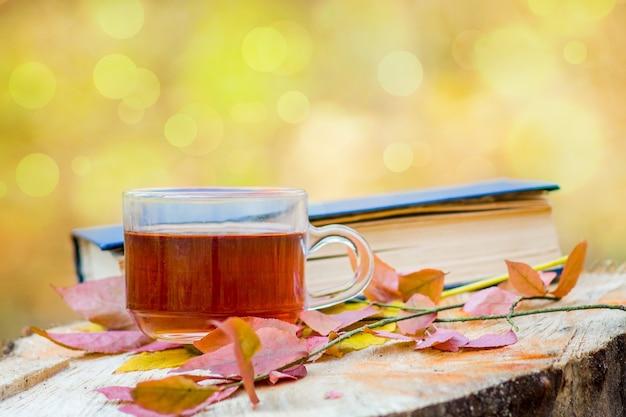 Uma xícara de chá, folhas de outono e um livro na floresta em um toco