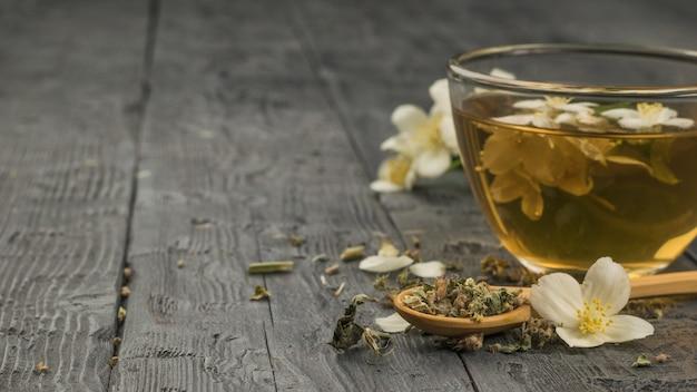 Uma xícara de chá fresco com flores de jasmim em uma mesa de madeira preta. lugar para texto.