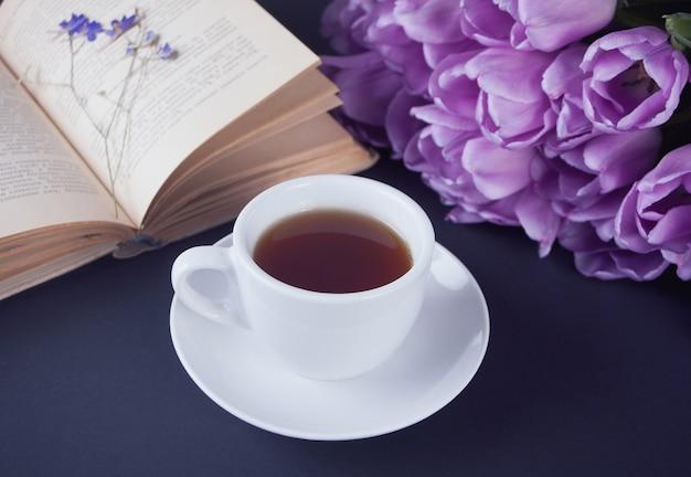Uma xícara de chá, livro e tulipas violetas na mesa
