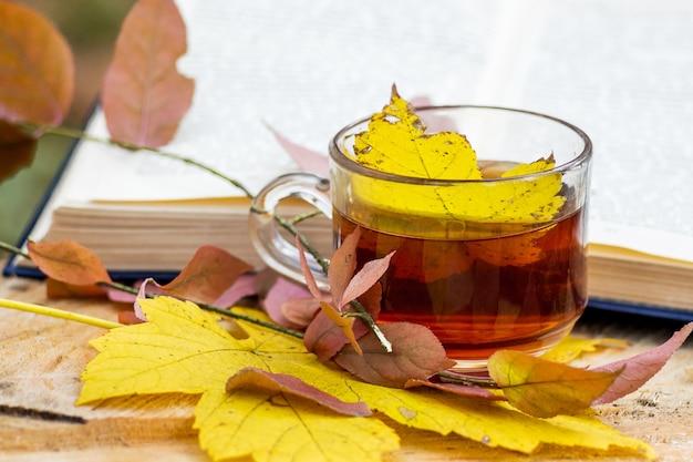 Uma xícara de chá, na qual caiu uma folha de bordo amarela, perto do livro na floresta de outono