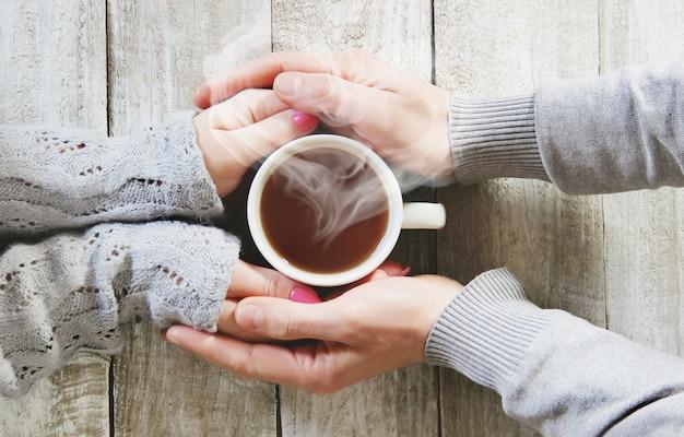 Uma xícara de chá nas mãos de um homem e uma mulher. foco seletivo.
