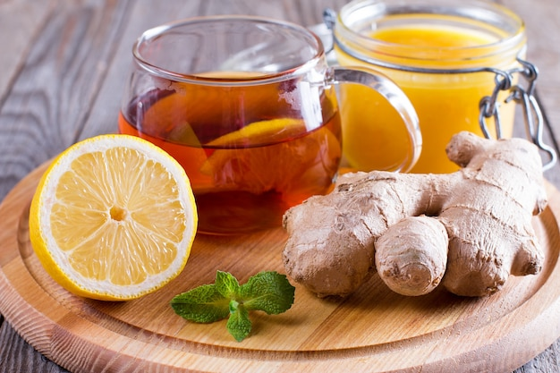 Uma xícara de chá natural com gengibre, limão, hortelã e mel na madeira