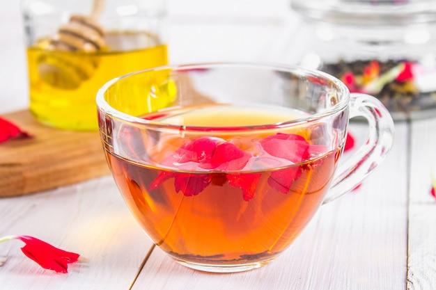 Uma xícara de chá, no fundo de um banco de mel e um frasco com um preto