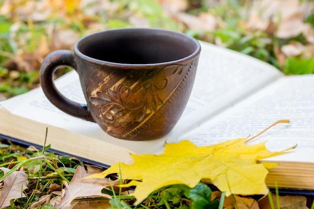 Uma xícara de chá ou café e uma folha de bordo amarela em um livro aberto no outono na floresta. descanse e lendo um livro na natureza_