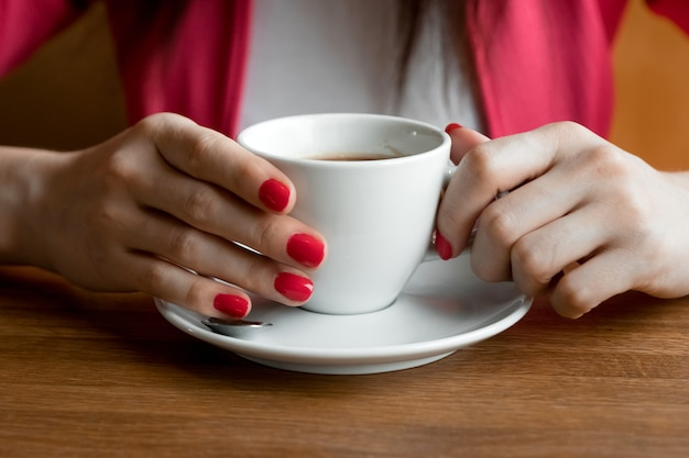 Uma xícara de chá ou café nas mãos de uma mulher, manicure rosa, close-up