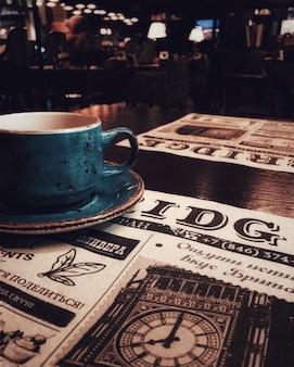 Uma xícara de chá ou café, um bar, um restaurante, um jornal.