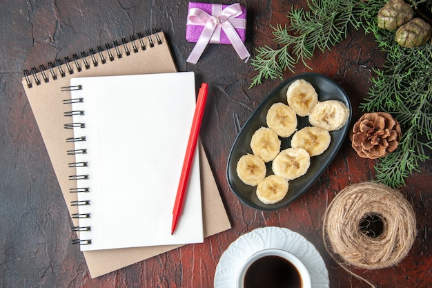 Uma xícara de chá preto, acessórios de decoração de ramos de abeto e presente e caderno com caneta e banana picada em fundo escuro