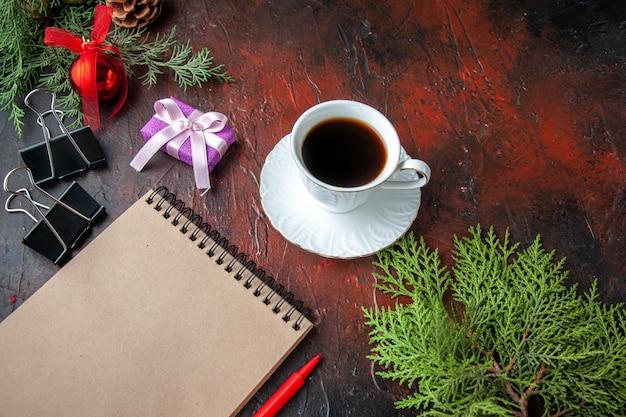 Uma xícara de chá preto, acessórios de decoração de ramos de abeto e um presente ao lado de um caderno com uma caneta em fundo escuro