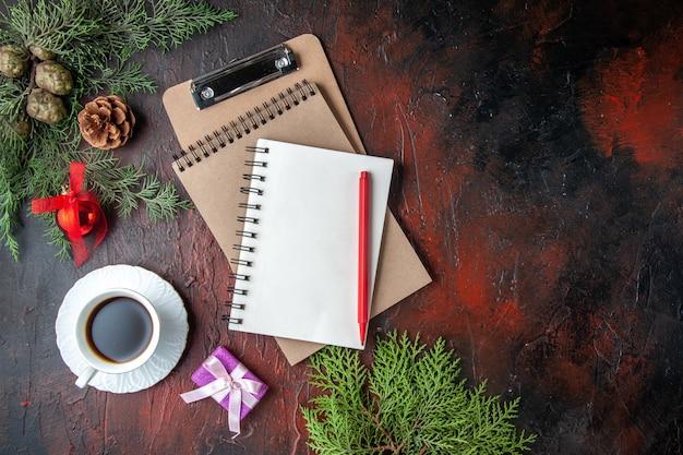 Uma xícara de chá preto, acessórios de decoração de ramos de abeto e um presente ao lado do caderno com fundo escuro de penon