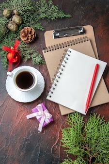Uma xícara de chá preto com acessórios de decoração de ramos de abeto e um presente ao lado de um caderno com uma caneta na filmagem de fundo escuro