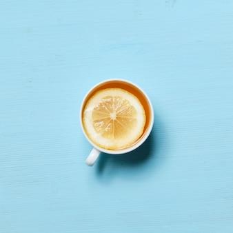 Uma xícara de chá preto com uma fatia de limão na superfície azul pálida