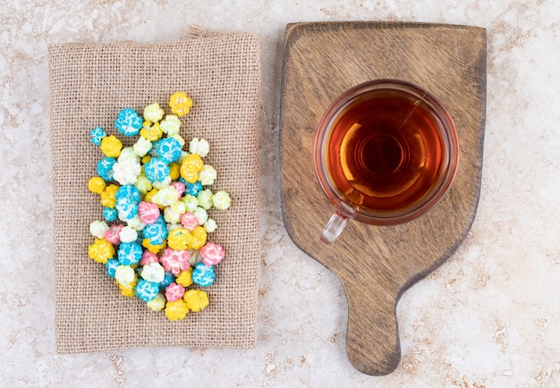 Uma xícara de chá quente com doces coloridos