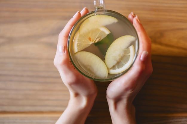 Uma xícara de chá quente com hortelã e limão nas mãos das mulheres