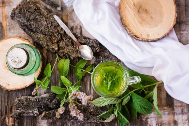 Uma xícara de chá quente com hortelã em uma mesa de madeira, vista superior