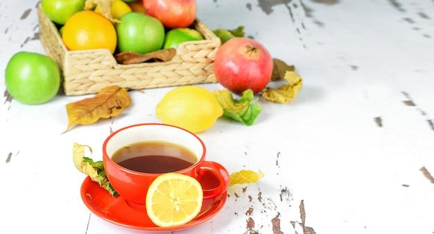 Uma xícara de chá quente com limão, uma pilha de frutas cítricas na cesta na mesa rústica de madeira