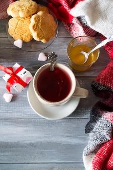 Uma xícara de chá quente com mel e biscoitos com uma manta.