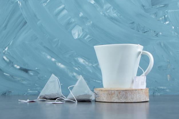 Uma xícara de chá quente com saquinhos de chá.