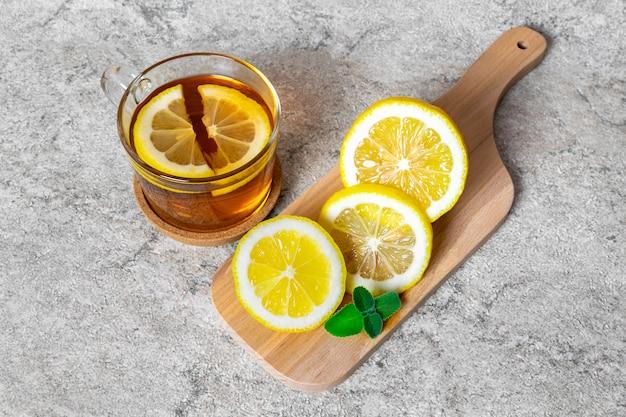 Uma xícara de chá quente com uma fatia de limão e hortelã para o tratamento da doença em uma tábua de madeira sobre uma mesa de pedra.