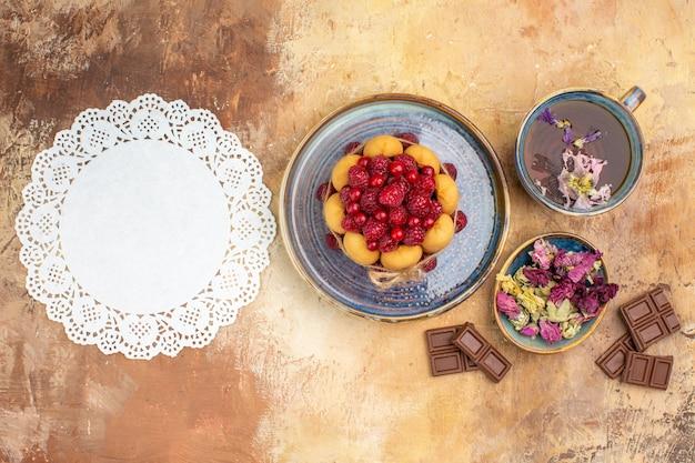 Uma xícara de chá quente de ervas, bolo macio com frutas, flores, barras de chocolate e guardanapo