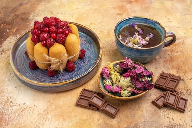 Uma xícara de chá quente de ervas bolo macio com frutas flores e barras de chocolate na mesa de cores misturadas