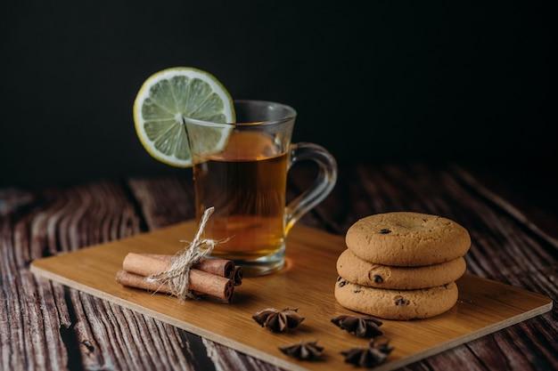Uma xícara de chá quente de frutas ou vinho quente em uma placa de madeira. perto estão biscoitos, canela e anis estrelado. copie o espaço.