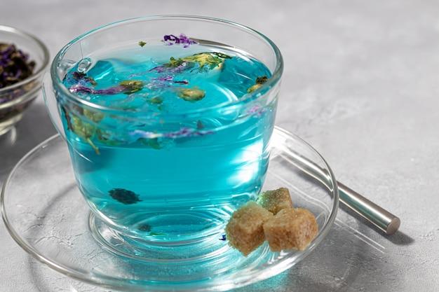 Uma xícara de chá quente e azul com flores de ervilha. ervilhas azuis. para uma bebida saudável, desintoxica o corpo. mesa cinza.