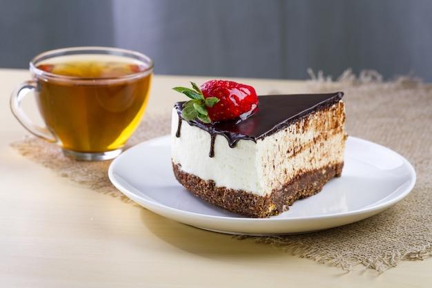 Uma xícara de chá quente e uma fatia de bolo doce com morangos frescos e cobertura de chocolate pingando em um prato branco.