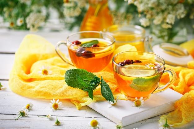 Uma xícara de chá saudável, um pote de mel e flores.
