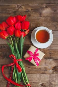 Uma xícara de chá tulipas vermelhas padrão e caixa de presente na mesa de madeira