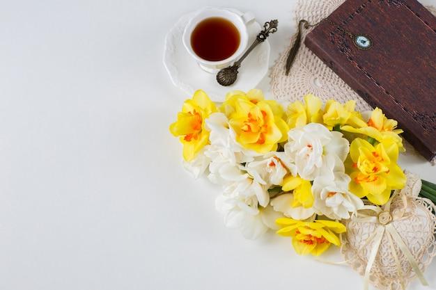 Uma xícara de chá, um livro, um buquê de narcisos e um coração rendado