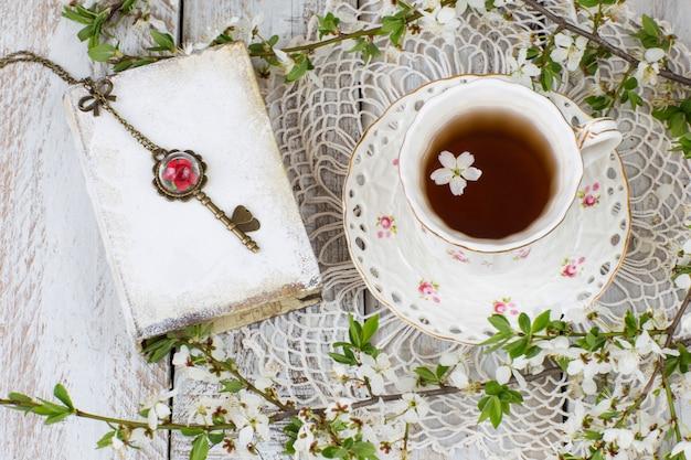 Uma xícara de chá, um livro, uma chave antiga, uma toalha de mesa de renda e ramos de cereja florida