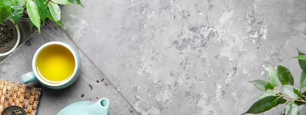 Uma xícara de chá verde em uma xícara azul sobre um fundo cinza de concreto.