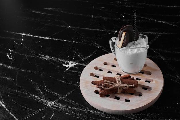 Uma xícara de chantilly com biscoitos.
