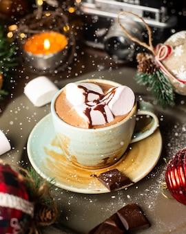 Uma xícara de chocolate quente com marshmallows e calda de chocolate