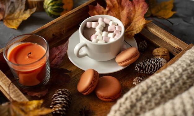 Uma xícara de chocolate quente com marshmallows em uma bandeja de madeira com biscoitos de pinha e folhas caídas