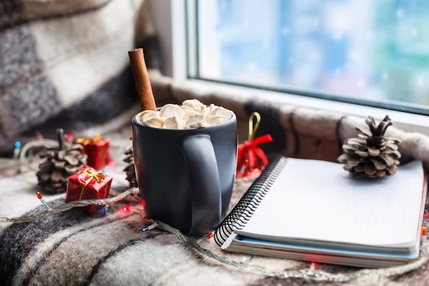 Uma xícara de chocolate quente e marshmallows na janela. conceito de ano novo