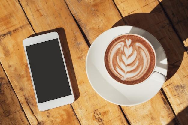 Uma xícara de chocolate quente ou chocolate e telefone celular na mesa de madeira, vista superior, copie o espaço.