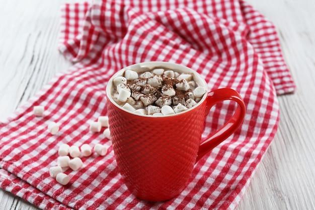 Uma xícara de chocolate saboroso e marshmallow em um fundo de guardanapo xadrez