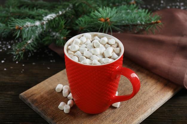 Uma xícara de chocolate saboroso e marshmallow na mesa